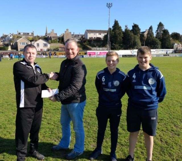 Mechanics head coach Charlie Brown accepting the cheque from Ian Wood with under-15 players Lewis McIntosh and Daniel Henderson.