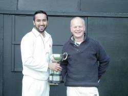Forres St Lawrence captain Pat Dhami receives the trophy from NoSCA president Mike Fox.
